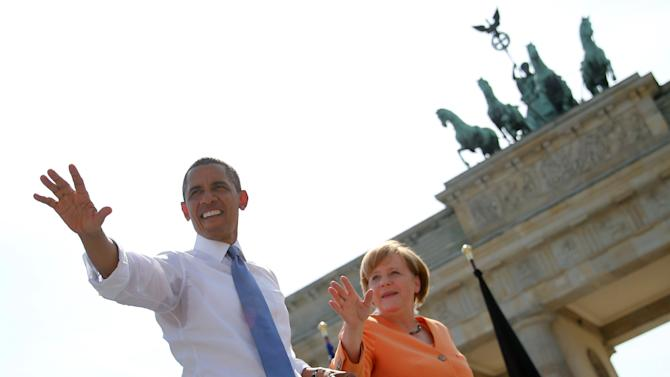 US President Barack Obama, left, waves to invited guests next to German Chancellor Angela Merkel . right, in front of Brandenburg Gate at Pariser Platz in Berlin, Germany Wednesday June 19, 2013. , On the second day of his visit to Germany, Obama met with German President Joachim Gauck and Chancellor Angela Merkel and delivered a speech at Brandenburg Gate. (AP Photo/Michael Kappeler,Pool)