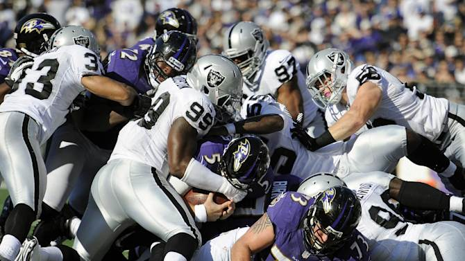 Baltimore Ravens quarterback Joe Flacco (5) falls into the end zone for a touchdown in the first half of an NFL football game against the Oakland Raiders in Baltimore, Sunday, Nov. 11, 2012. (AP Photo/Nick Wass)