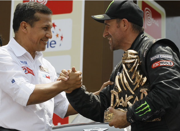 Mini driver Stephane Peterhansel, of France, right, shakes hands with Peru's President Ollanta Humala after receiving his first place trophy at the 2012 Argentina-Chile-Peru Dakar Rally podium ceremon