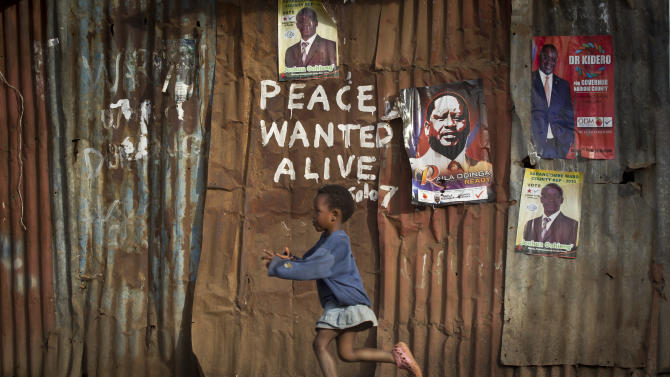 FILE - In this Wednesday, March 6, 2013 file photo, a young girl runs past pro-peace graffiti written during the post-election violence of the previous election in 2007 and a poster of presidential candidate Raila Odinga, center-right, in the Kibera slum of Nairobi, Kenya. Kenyan President Uhuru Kenyatta received late Tuesday, May 21, 2013 the long-awaited report from the Truth, Justice and Reconciliation Commission, which was established as part of a reform process aimed at preventing a repeat of the 2007-08 post-election violence in which more than 1,000 people were killed. (AP Photo/Ben Curtis, File)