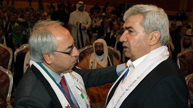 Syrian regime opponent Riad Seif, right, shakes hands with Syrian National Council (SNC) chief Abdel Basset Seda during the meeting of the General Assembly of the Syrian National Council in Doha, Qatar, Tuesday, Nov. 6, 2012. (AP Photo/Osama Faisal)