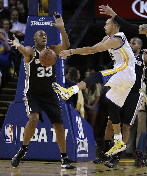 Golden State Warriors' Stephen Curry, right, passes away from San Antonio Spurs' Boris Diaw (33) during the first half of an NBA basketball game, Thursday, Dec. 19, 2013, in Oakland, Calif