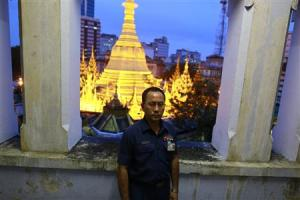 Toe Aung, deputy head of urban planning, poses for a photo at the Yangon City hall, with the lit Sule Pagoda seen behind him, in Yangon