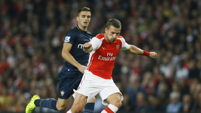 Arsenal's Lukas Podolski, right, controls the ball ahead of Southampton's Dusan Tadic during the English League Cup soccer match between Arsenal and Southampton at Emirates Stadium in London, Tuesday, Sept. 23, 2014. (AP Photo/Kirsty Wigglesworth)