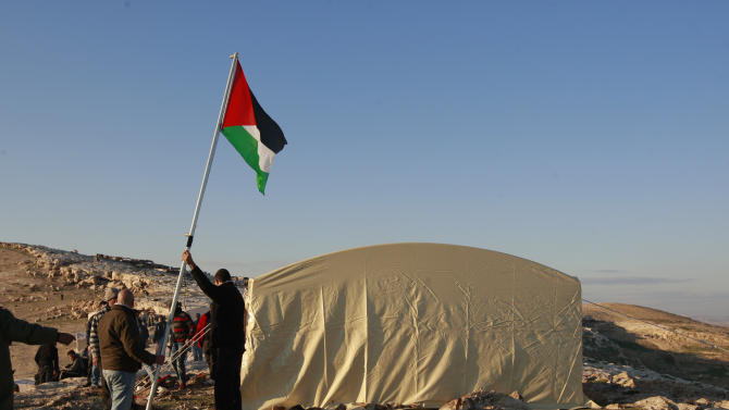 A Palestinian activist raises a Palestinian flag in the new 'outpost ' of Bab al-Shams (Gate of the Sun) in an area known as E1, near Jerusalem, Friday, Jan 11, 2013. Palestinian activists pitched tents in the West Bank on Friday to protest Israeli plans to build a large Jewish settlement on a key route through the territory. The E-1 settlement would block east Jerusalem from its West Bank hinterland — both territories captured by Israel during the 1967 Mideast war. (AP Photo/Majdi Mohammed)