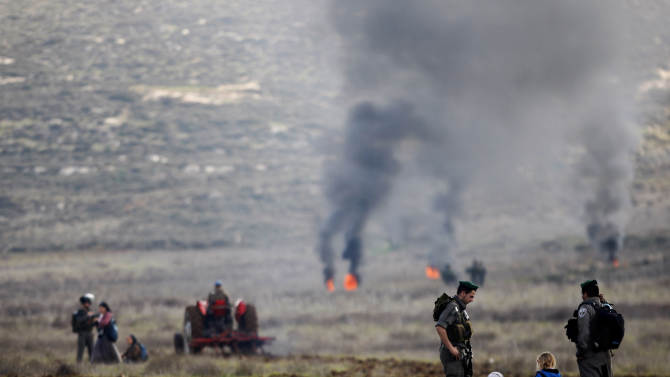 Surrounded by Israeli border police Jewish settlers from the Esh Kodesh settlement outpost sit in a field in an attempt to prevent Palestinians from farming land in the northern West Bank, Wednesday, Jan. 2, 2013. Both the settlers and Palestinians living in the area claim ownership of the disputed land. (AP Photo/Majdi Mohammed)