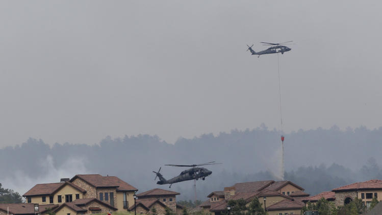 Army helicopters drop water on the Black Forest wildfire behind houses on the Flying Horse Ranch in Colorado Springs, Colo., on Thursday, June 13, 2013. The residential area was evacuated Thursday. Over 350 homes have been destroyed by the fire since Tuesday. (AP Photo/Ed Andrieski)