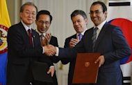South Korean Trade Minister Bark Tae-ho (L) and his Colombian counterpart Sergio Diaz Granados shake hands after the signing of a Free Trade Agreement beetwen the two countries as their respective presidents Lee Myung-bak (2-L) and Juan Manuel Santos (2-R) applaude, during a ceremony at Narino presidential palace in Bogota, on June 25