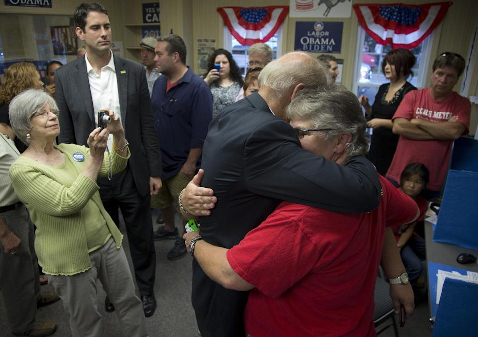 Vice President Joe Biden hugs Cathy Pool and her partner of over 20 years Mendy Yates, in the middle of the hug, as he visits a campaign field office, Saturday, Sept. 8, 2012, in Chilicothe, Ohio.  (AP Photo/Carolyn Kaster)