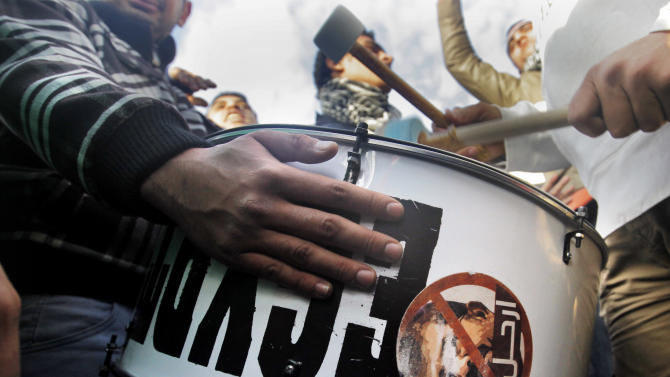 Egyptian protesters play on a drum with a sign with a picture of Egyptian President Morsi, and Arabic reading ' leave.' before clashes in front of the presidential palace in Cairo, Egypt, Friday, Feb. 1, 2013.  Thousands of Egyptians marched across the country, chanting against the rule of the Islamist President Mohammed Morsi, in a fresh wave of protests Friday, even as cracks appeared in the ranks of the opposition after its political leaders met for the first time with the rival Muslim Brotherhood. (AP Photo/Amr Nabil)