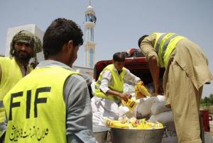 Volunteers arrange food packs for people fleeing military offensive in North Waziristan, in Nurar village