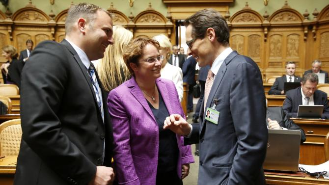 SVP's newly elected National Councillor Koeppel talks with Martullo-Blocher and Dettling before the swearing-in ceremony of the Swiss Parliament in Bern
