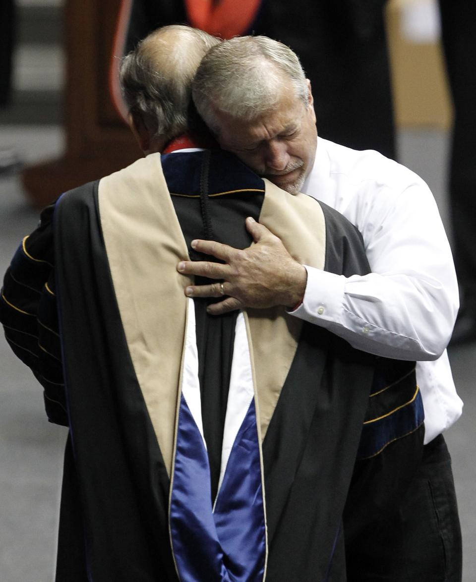 Allan Sigler hugs University President Dr. Robert Witt after he accepts the degree from the University of Alabama on behalf of his daughter Morgan Sigler on Saturday, Aug. 6, 2011 in Tuscaloosa, Ala. Morgan lost her life when a tornado ripped through Tuscaloosa on April 27, 2011. (AP Photo/Butch Dill)