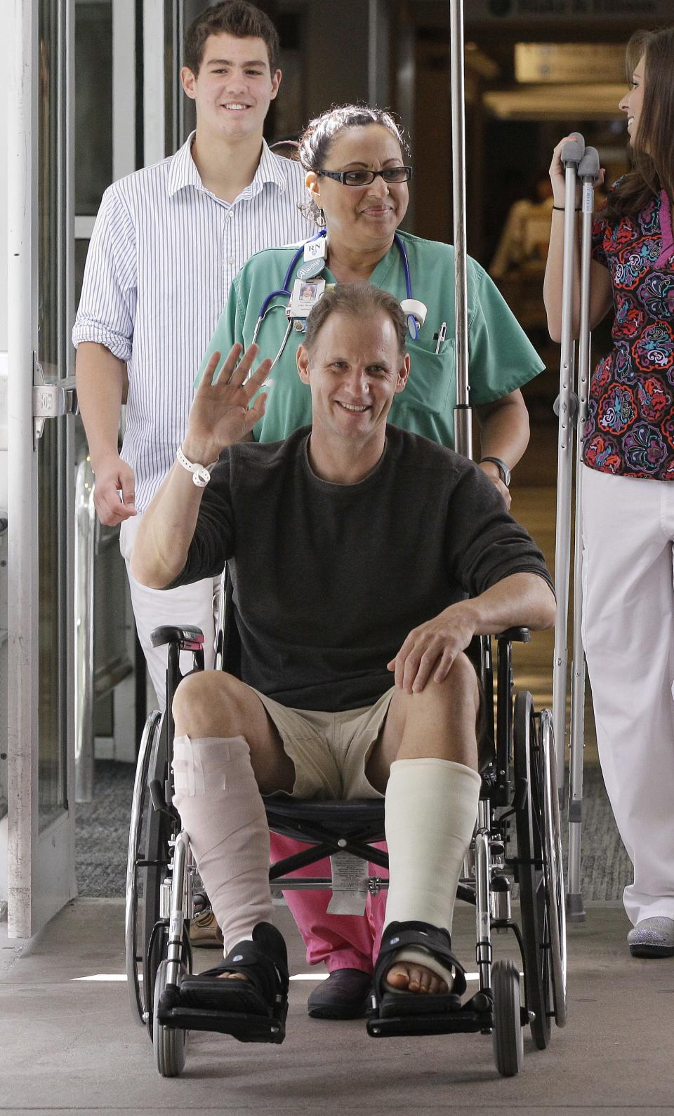 Christopher Myers, of Denver, is wheeled into a media availability at Massachusetts General Hospital upon his discharge after receiving treatment as the result of a shark attack in Boston, Friday, Aug. 3, 2012. Myers was bitten off Ballston Beach in Truro on Monday. (AP Photo/Stephan Savoia)