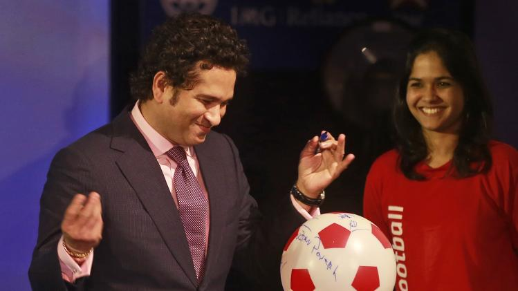 Sachin Tendulkar, former Indian cricketer and co-owner of Kerala Blasters Football Club, signs a soccer ball during official launch of the Indian Super League (ISL) in Mumbai, India, Thursday, Aug. 28, 2014. The ISL, an initiative to popularize soccer in the country, is scheduled to begin Oct. 12. (AP Photo/Rafiq Maqbool)