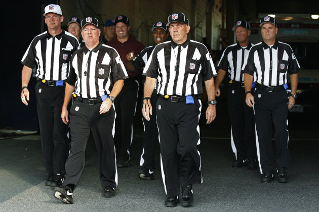 FILE - In this Aug. 9, 2012, file photo, officials walk towards the field for an NFL football game between the Buffalo Bills and the Washington Redskins in Orchard Park, N.Y. The NFL and referees' union reached a tentative agreement on Wednesday, Sept. 26, to end a three-month lockout that triggered a wave of frustration and anger over replacement officials and threatened to disrupt the rest of the season. (AP Photo/Bill Wippert, File)