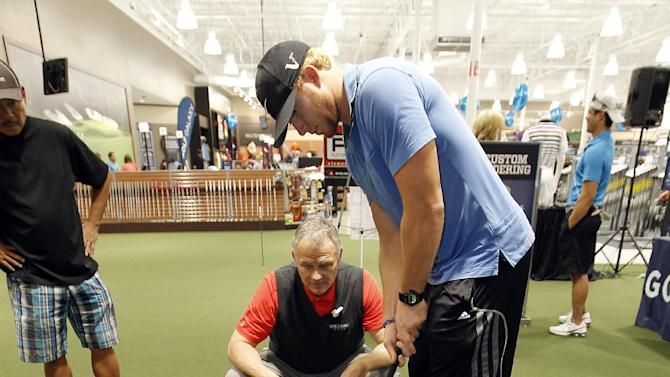 Sam Froggatte with Eye-Line Golf, center, shows Nick Stephens how to line up properly with the hole at Golf Galaxy's grand opening in Grapevine, Texas, on Friday, November 9, 2012. (Brandon Wade/AP Images for Golf Galaxy)