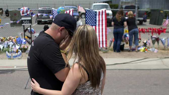 Joanne Barringer, right, comforts her husband Dave Barringer, of Las Vegas, after hanging a T-shirt on the fence outside the Granite Mountain Interagency Hot Shot Crew fire station, Monday, July 1, 2013 in Prescott, Ariz. Barringer, who said he works as a wild land firefighter for the U.S. Forest Service said he was friends with many of the 19 Hotshots who were killed Sunday when an out-of-control blaze overtook the elite group near Yarnell, Ariz. (AP Photo/Julie Jacobson)