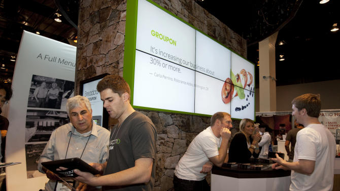 Groupon employee shows Breadcrumb to a visitor at their booth at the National Restaurant Association Tradeshow at McCormick Place, on Sunday, May 19, 2013 in Chicago, IL. Groupon highlights the company's marketing and Breadcrumb by  Groupon point-of-sale and payments at the tradeshow. (John Konstantaras / AP Images for Groupon)