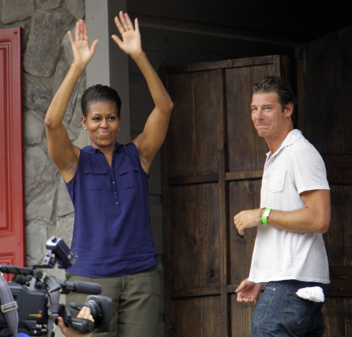 First lady Michelle Obama waves as she and Ty Pennington, host of Extreme Makeover Home Edition, enter the Jubilee House during the taping of an episode in Fayetteville, N.C., Thursday, July 21, 2011. (AP Photo/Gerry Broome)