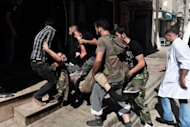 Free Syria Army fighters carry a wounded comrade into a hospital in Aleppo, Syria's second largest city