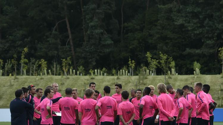 Barcelona's coach Luis Enrique speaks with his players during a training session at St. George's Park near Burton on Trent