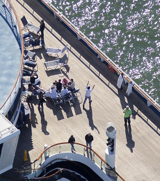 Passengers congregate on an upper deck of the disabled Carnival Lines cruise ship Triumph as it is towed to harbor off Mobile Bay, Ala., Thursday, Feb. 14, 2013. The ship with more than 4,200 passenge
