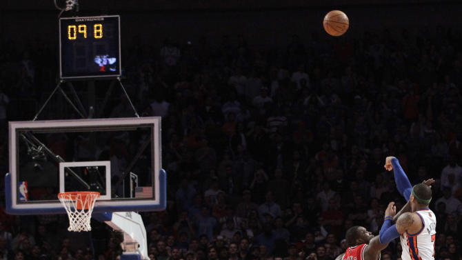 New York Knicks' Carmelo Anthony, right, shoots a 3-point basket in the closing seconds of overtime, past Chicago Bulls' Luol Deng during an NBA basketball game, Sunday, April 8, 2012, at Madison Square Garden in New York. The Knicks defeated the Bulls 100 to 99. (AP Photo/Mary Altaffer)