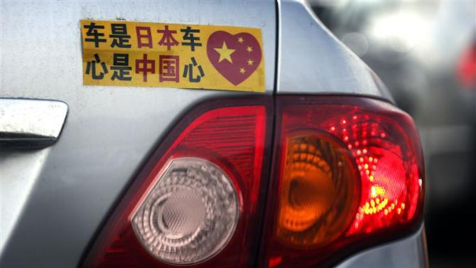 File photo of a Toyota car with sticker attached to the rear seen along a main road in central Beijing