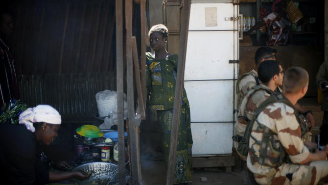 French troops sit in a cafe in Niono, some 400 kilometers (249 miles) north of the capital Bamako, Sunday, Jan. 20, 2013. The Malian military announced late Saturday that the government was now controlling Diabaly, marking an important accomplishment for the French-led offensive to oust the extremists from northern and central Mali. (AP Photo/Jerome Delay)
