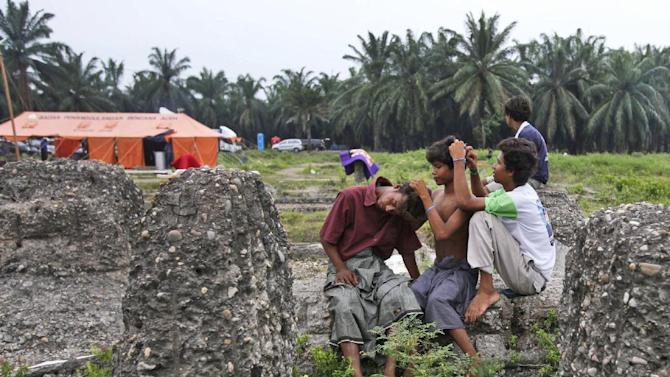 Rohingya migrants pick lice from each other's hair at their temporary shelter in Bayeun, Aceh province, Indonesia Friday, May 22, 2015. In the past three weeks, thousands of refugees and migrants have washed ashore in Malaysia, Indonesia and Thailand, according to the International Organization for Migration. Half are Rohingya and the rest are from Bangladesh, the IOM said. The U.N. refugee agency estimates more than 3,000 others may still be at sea. (AP Photo/Binsar Bakkara)