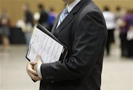 A job seekers holds his binder filled with resumes at the Phoenix Convention Center in Phoenix, Arizona
