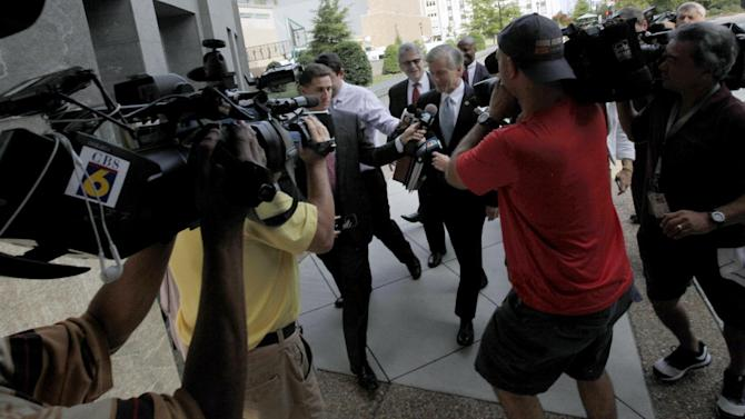 Former Virginia Gov. Bob McDonnell, center, is surrounded by media as he walks to the federal courthouse in Richmond, Va. on Monday, Aug. 11, 2014, as his corruption trial enters its third week. McDonnell and his wife are charged in a 14-count indictment with accepting more than $165,000 in gifts and loans from the former CEO of a nutritional supplements company in exchange for promoting his products. They could face decades in prison if convicted. (AP Photo/Richmond Times-Dispatch, Bob Brown)