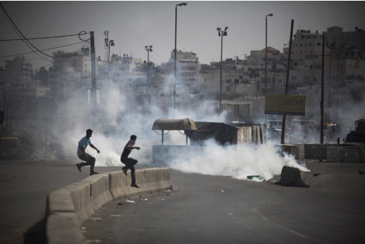 Palestinian demonstrators run from tear gas fired by Israeli soldiers, not seen, during a protest at the Qalandia checkpoint between the West Bank city of Ramallah and Jerusalem, Wednesday, Sept. 21, 2011. Palestinians clashed with Israeli security forces in Qalandia Wednesday, as thousands of flag-waving Palestinians rallied in towns across the West Bank to show support for their president's bid to win U.N. recognition of a Palestinian state. (AP Photo/Tara Todras-Whitehill)