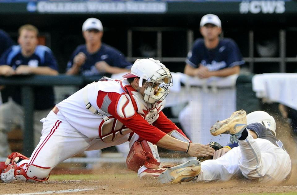 North Carolina's Brian Holberton, right, beats the tag at home plate against North Carolina State catcher Brett Austin on a sacrifice fly by Michael Russell in the fourth inning of an NCAA College World Series elimination baseball game in Omaha, Neb., Thursday, June 20, 2013. (AP Photo/Eric Francis)