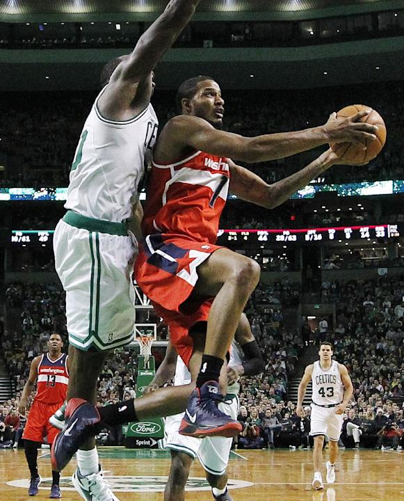 Washington Wizards' Trevor Ariza (1) shoots against Boston Celtics' Brandon Bass (30) in the third quarter of an NBA basketball game in Boston, Saturday, Dec. 21, 2013. The Wizards won 106-99