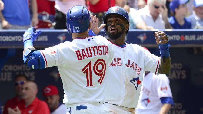 Toronto Blue Jays' Jose Bautista is congratulated by teammate Jose Reyes after hitting a two-run home run against the Boston Red Sox during the second inning of a baseball game in Toronto on Wednesday, July 1, 2015. (Frank Gunn/The Canadian Press via AP)