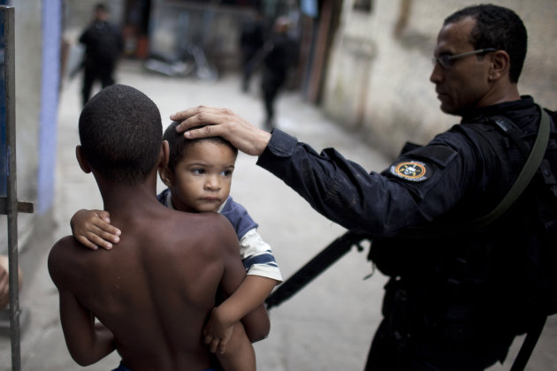 A Brazilian police officer pats a boy on the head while on patrol in the Rocinha slum in Rio de Janeiro, Brazil, Sunday Nov. 13, 2011. Elite police units backed by armored military vehicles and helico