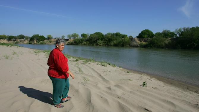 File - In this March 21, 2008 file photo, Los Ebanos resident Aleida Flores Garcia walks toward the Rio Grande on her property. If Congress agrees on a comprehensive immigration reform bill, it will probably include a requirement to erect fencing that would wrap more of the nation's nearly 2,000-mile Southwest border in tall steel columns. But the mandate would essentially double down on a strategy that the Customs and Border Protection agency isn't even sure works. And the prospect of the government seizing more land offends many property owners here in the southernmost tip of Texas, where hundreds of people already lost property during the last fence construction spree. (AP Photo/Alex Jones, File)