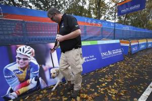 A security guard and bomb sniffing dog patrol the area near the finish line of the New York City Marathon