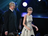 "T Bone Burnett, left, and Taylor Swift, right walk to the stage to accept the award for song written for visual media for ""Safe and Sound"" (From The Hunger Games) at the 55th annual Grammy Awards on Sunday, Feb. 10, 2013, in Los Angeles. (Photo by John Shearer/Invision/AP)"