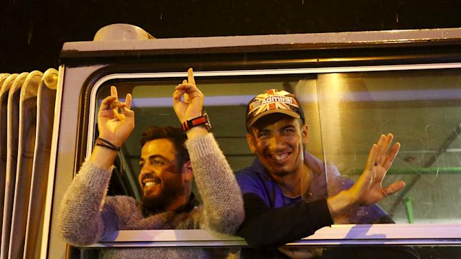Migrants gesture on a bus bound for Austria and Germany, next to the Keleti train station in Budapest