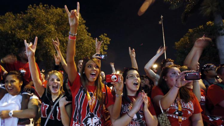Northern Illinois fans cheer the arrival of the team before the Orange Bowl NCAA college football game against Florida State, Tuesday, Jan. 1, 2013, in Miami.  (AP Photo/Alan Diaz)