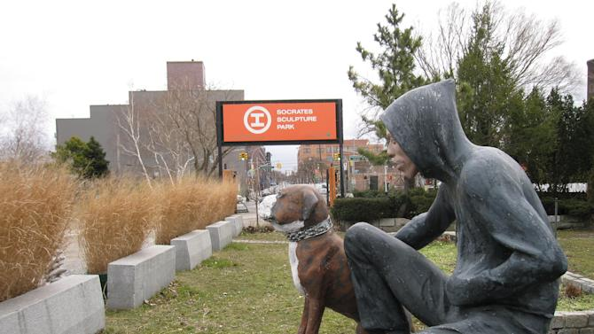 """This March 6, 2013 photo shows """"Raymond & Toby,"""" a 1994 sculpture by John Ahearn at Socrates Sculpture Park in the Astoria section of the Queens borough of New York.  The waterfront park is one of several art-related attractions in Astoria and the adjacent neighborhood of Long Island City. A boom in moderately priced hotels in Long Island City has begun luring tourists to the area. Along with museums, parks, hotels and ethnic restaurants, the area is still home to a large industrial base, from auto shops to factories. (AP Photo/Beth J. Harpaz)"""