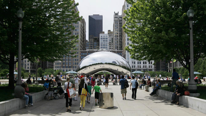 "In this Wednesday, June 13, 2012, photo, visitors at Chicago's Millennium Park enjoy the sculpture ""Cloud Gate,"" also known as ""The Bean"" on Wednesday, June 13, 2012 in Chicago. Millennium Park is one of several free activities/things/places visitors can enjoy in Chicago. (AP Photo/Charles Rex Arbogast)"