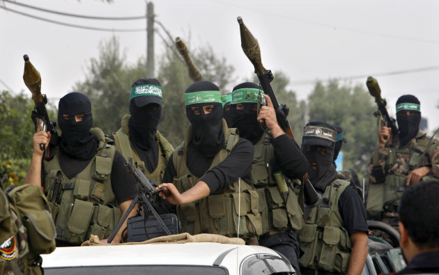 Palestinian militants of the Izzedine Al-Qassam Brigades, the armed wing of Hamas, attend funerals of five Hamas militants in Mugharka village, central Gaza Strip, Thursday, Nov. 22, 2012. Five Hamas