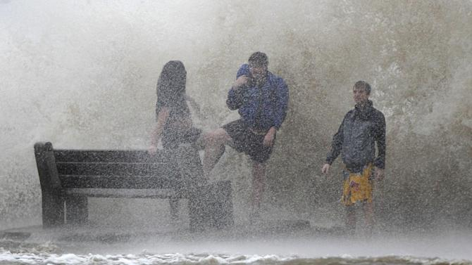 People walk in the storm surge from Isaac, on Lakeshore Drive along Lake Pontchartrain, as the storm approaches landfall, in New Orleans, Tuesday, Aug. 28, 2012. The storm was arriving at the seventh anniversary of Hurricane Katrina, which devastated Louisiana and Mississippi when it struck on Aug. 29, 2005. (AP Photo/Gerald Herbert)