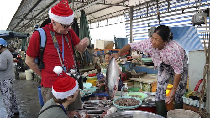Donning Santa hats, Ed Prosser, top left, and his wife Penny Spelling of London, England, explore a market in the Vietnamese town of Sa Dec in the Mekong Delta Thursday, Dec. 25, 2014. The couple is on a shore excursion by the Uniworld cruise ship River Orchid. (AP Photo/Nick Ut)