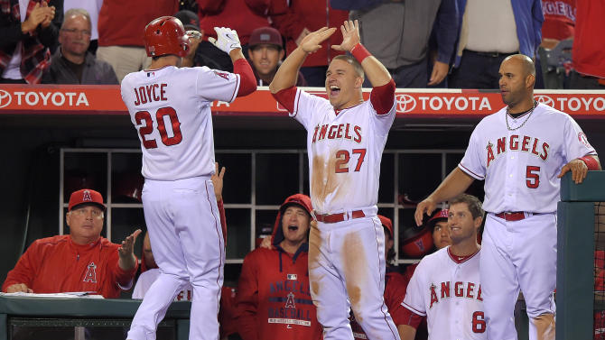 Los Angeles Angels' Matt Joyce, left, is congratulated by Mike Trout, center, and Albert Pujols, right, after hitting a solo home run during the seventh inning of a baseball game against the Seattle Mariners, Monday, May 4, 2015, in Anaheim, Calif. (AP Photo/Mark J. Terrill)