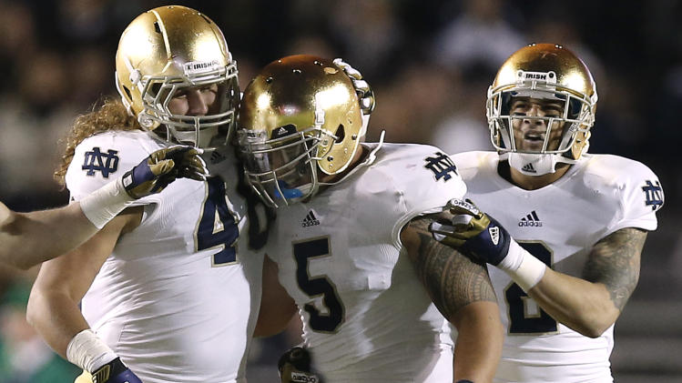Notre Dame linebacker Manti Te'o is congratulated by teammates Dan Fox and Bennett Jackson, right, after his interception during the second half of Notre Dame's 21-6 win over Boston College in a NCAA college football game in Boston Saturday, Nov. 10, 2012. (AP Photo/Winslow Townson)